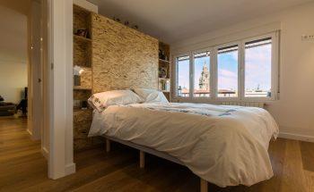 El dormitorio y el estudio están separados por un mueble de madera que hace las veces de cabecero y de estantería